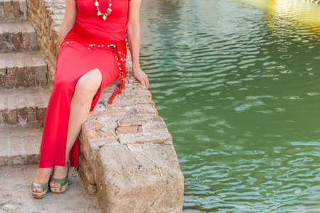 Comacchio, Little Venice in Italy, legs of sophisticated older woman sitting on the wall of a staircase of a brick bridge over the canal of a lagoon town in Italy