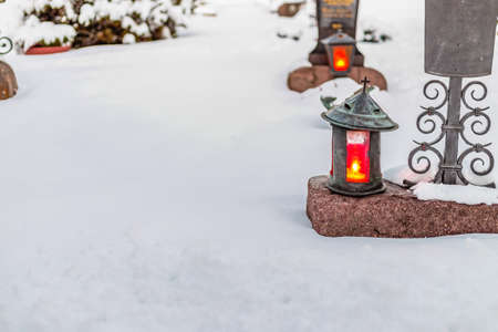 lighted: lighted candles in a snowy cemetery