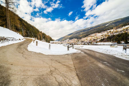 clic: country road leading through a winter mountain landscape. Stock Photo
