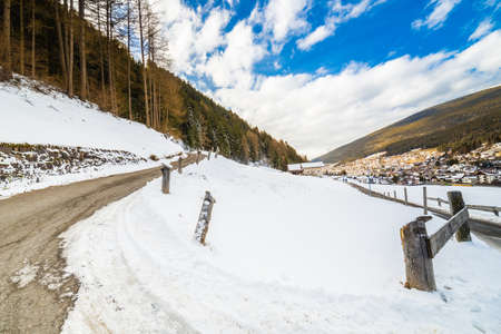 country road leading through a winter mountain landscape. Stock Photo