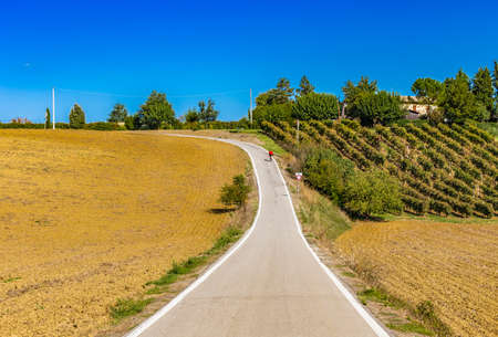 serpentine road through the plowed fields of the countryside of Tuscany and Emilia appenine Stock Photo