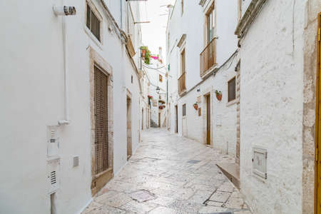the intricate lanes of whitewashed houses of Locorotondo, a town of Apulia in Italy Stock Photo - 116844489