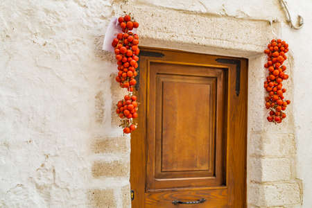 cluster house: Door of typical house in Ostuni, The White City, with Cluster of cherry tomatoes