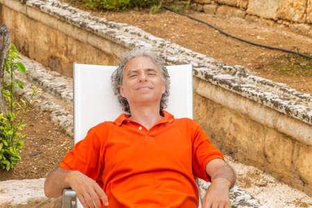 retired senior man resting blissfully lying on the recliner in the garden