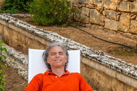 blissfully: retired senior man resting blissfully lying on the recliner in the garden