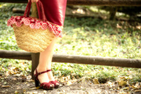 shapely: long and shapely female legs of a woman who is waiting in a park, she is wearing a red tube dress, high-heeled sandals and holding a flower-filled bag in country style Stock Photo