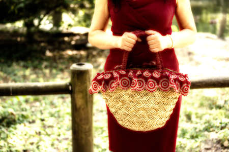 female hands holding a bag in a country style made of raffia and red cloth with white flowers, the woman dressed in a red sheath dress is waiting nervously in a park Stock Photo