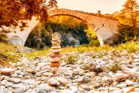 jorobado: pile of stones in front of 500 years old hunchback Renaissance bridge connecting two banks with single span in Italian Countryside Foto de archivo