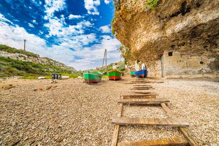 rowboats storage  on the stony and pebble beach in Italy