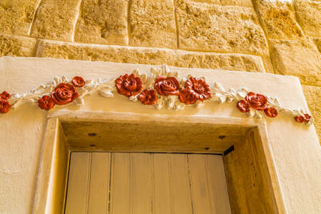 pediment: decorated  red flowers and roses on a pediment of a door Stock Photo