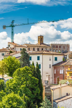 panorama of medieval village under construction in the countryside of Romagna in Italy with worker on the roof