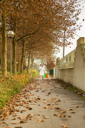 avenues: Happy attractive woman talking on phone while walking with shopping bags in avenues in autumn