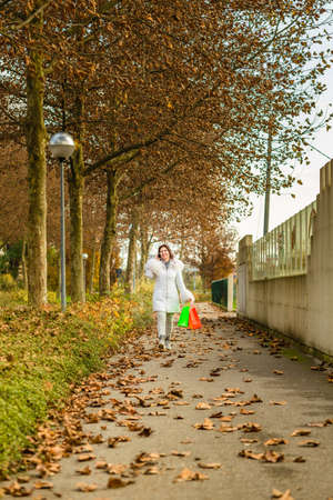 avenues: Happy menopausal woman with wrinkles talking on phone while walking with shopping bags in avenues in autumn