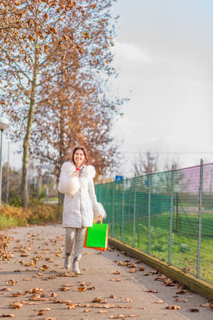 avenues: Happy attractive woman holding red flower while walking with shopping bags in avenues in autumn Stock Photo