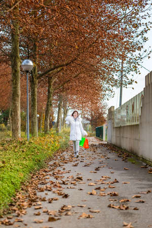 avenues: Happy menopausal woman talking on phone while walking with shopping bags in avenues in autumn