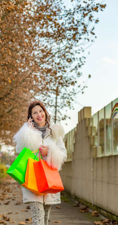 Happy menopausal woman talking on phone while walking with shopping bags in tree-lined street in autumn