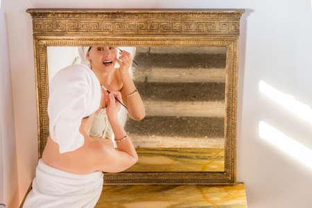 comely: comely menopausal woman with hair and body in towels applying makeup eyes being reflected in an antique mirror