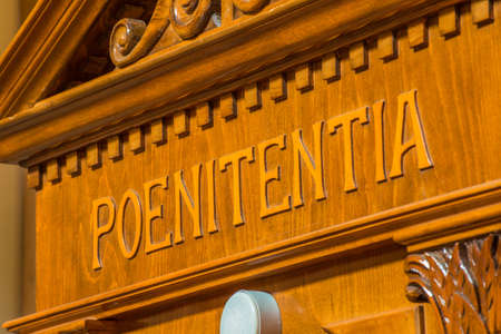sins: the Latin word poenitentia meaning repentance engraved on a wooden confessional