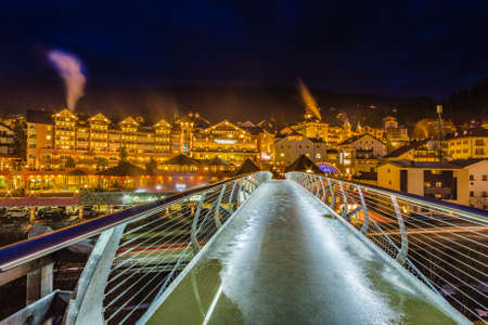 night view of modern bridge going to typical mountain village in Italy