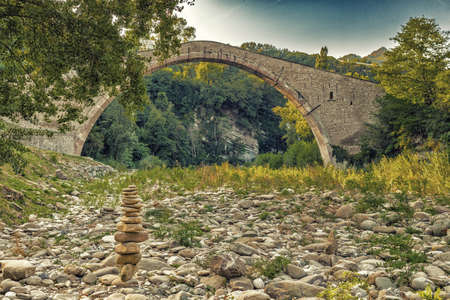 pile of stones in front of 500 years old hog backed Renaissance bridge connecting two banks with single span in Italian Countryside