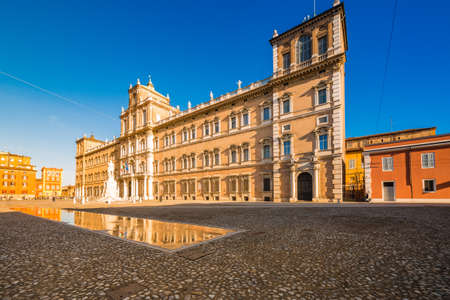 mirror of water of fountains in front of baroque Royal Palace in Modena, Italy Editorial