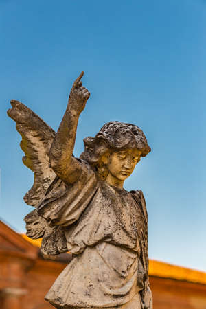 statue of young angel looking down and raising finger up to the sky Stock Photo
