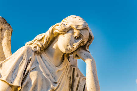 statue of sad and grieved angel looking down and sustaining her reclined head with hand Stock Photo