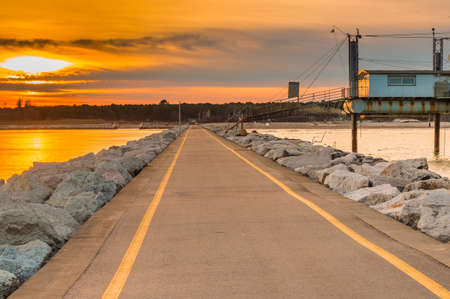 sunset on the pier paved road leading to the beach in Italy Stock Photo