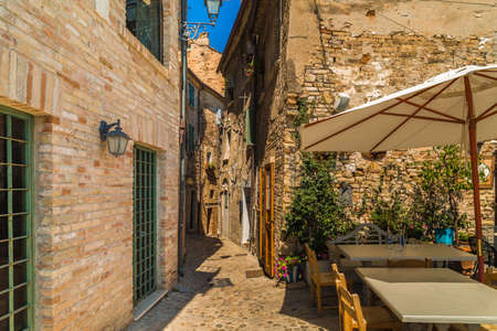 alley with tables and chairs near ancient buildings of a typical village in the Marche region in Italy