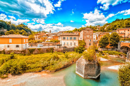 the serenity of a quiet village in the hills of Romagna countryside in Italy, while the cool waters of a placid river bathe the hamlet Stock Photo