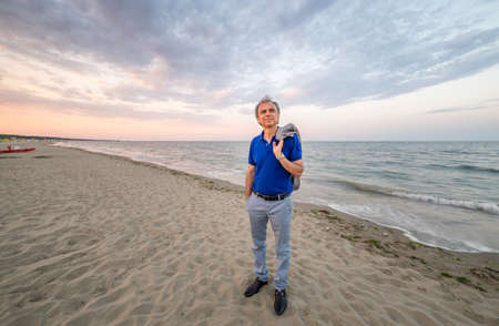 cuddled: Classy mature man on the beach with his jacket on his shoulder walking on shoreline and looking to the future, very relaxed and serene he enjoys the beauty of nature