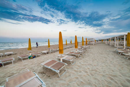 Sun loungers and closed umbrellas at a seaside resort of Emilia Romagna on the Adriatic Riviera in Italy, the calm and relaxed atmosphere of the summer holiday