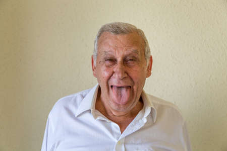 Emotional and goofy caucasian pensioner wearing white shirt grimacing, making mouths, sticking out his tongue at camera isolated on yellow wall background