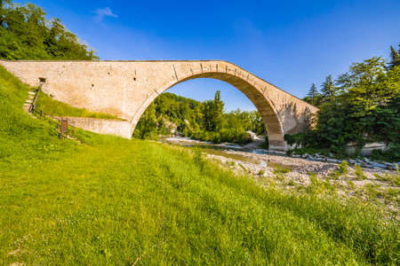 green grass to ancient XVI bridge with donkey back structure, one of wonders of Italy