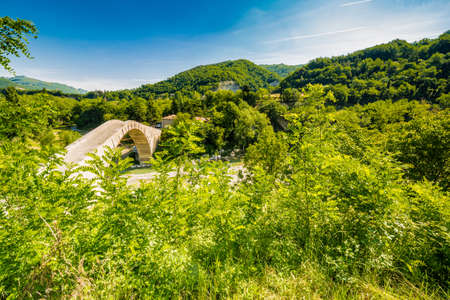 green countryside around ancient bridge in Italy