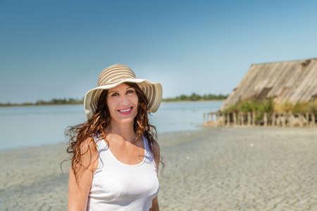 わら小屋の太陽分割ビーチの広い帽子で非常に良い形で魅力的な成熟した巨乳女性