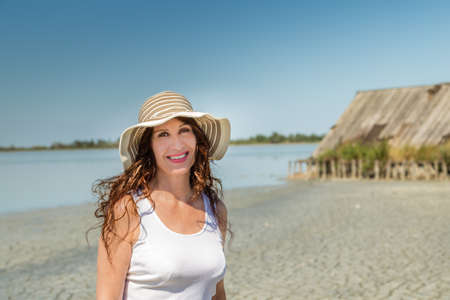 Attractive mature busty woman in very good shape with wide hat on a sun split beach with  straw hut Reklamní fotografie