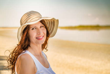 Handsome menopausal woman in very good shape with wide hat smiling on a sun split beach
