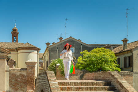 classy house: Beautiful mature tourist with red wide hat enjoying shopping in a picturesque medieval village in Europe, Comacchio,