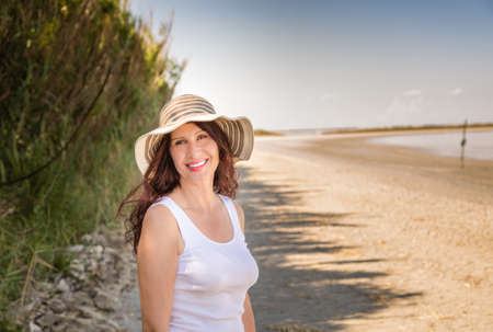 Handsome mature busty woman in very good shape with wide hat smiling on a sun split beach