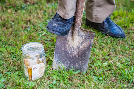 Burying a jar of money into the ground by digging a hole with a shovel