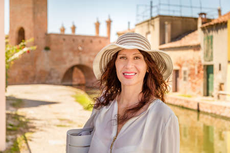 classy house: Caucasian happy woman in panama with Asian traits enjoying walking in Italian  lagoon city, Comacchio, known as The Little Venice. Stock Photo