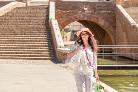 classy mature woman with wide hat and sunglasses near ancient bridge in Italy
