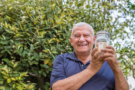 deposition: old man smiling while holding a jar full of euro banknotes on green nature background Stock Photo