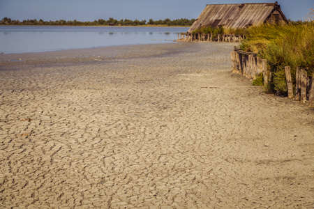 cracked clay soil beach with a straw hut  on clear lagoon water Stok Fotoğraf