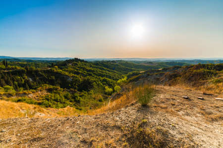 green weeds and arid rocks of lunar landscape of Senese Clays, region of badlands under the sun of Tuscany in Italy Фото со стока