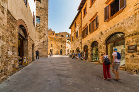 tourists shopping in street with typical stone buildings of the medieval village of San Gimignano near Siena under the sun of Tuscany