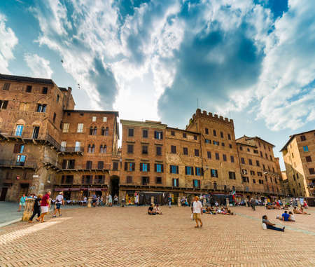 relaxing tourists enjoying main square in Siena, Italy under the sun of Tuscany