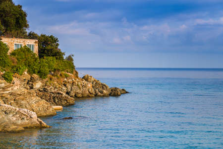 house on rocks on clear and blue sea of Island of Elba under the sun of Tuscany in Italy Stock Photo