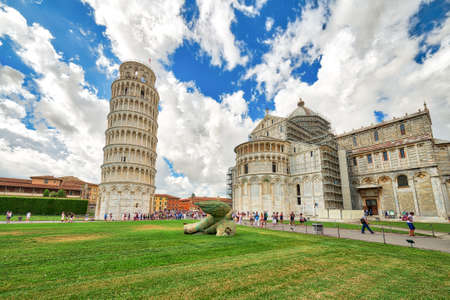 tourists in public Square of miracles in Pisa enjoying the leaning tower, one of the most famous wonders of Italy